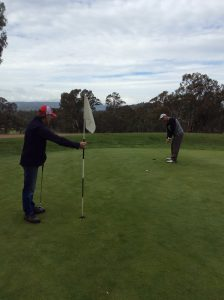 John Tanner putts on the 6th with Peter Williams on the flag-stick.